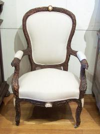 Carved black forest upholstered bark chair with boars heads c1880