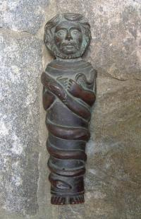 Primitive bronze figure with snake
